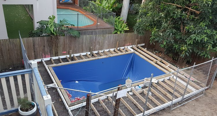The decking frame is now complete and the pool liner is installed. Notice that there was more rain, filling the pool before we were ready!!