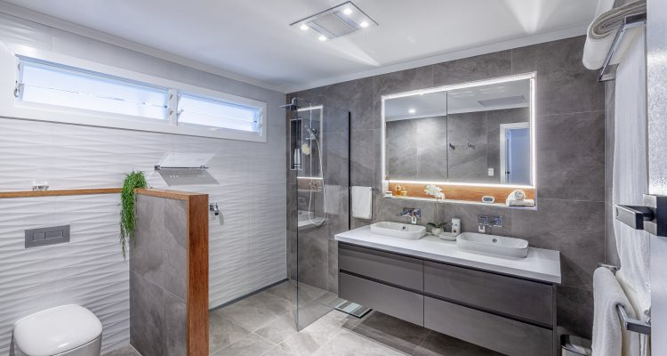 The separate toilet and bathroom were combined into one much larger, airier and brighter space. Bespoke timber features were crafted by Julian to complement the contemporary floor and wall tiles, and a modern frameless shower screen was installed.
