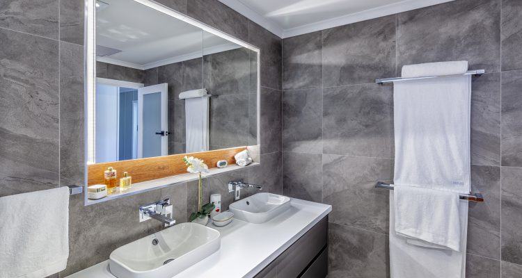 Double sinks were also installed over the new floating vanity unit, whilst the double mirror-door cabinet with LED backlit under-cabinet shelf was inset into the wall to give a more functional and streamlined finish to the room.The bespoke timber feature panel of the shelf softens the contemporary floor and wall tiles.