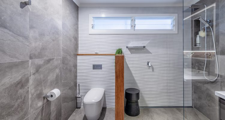Along with the feature panel of the under cabinet shelf, the bespoke timber panels on the toilet partition wall adds a unique and inviting feature in the bathroom.