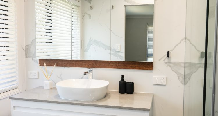The ensuite bathroom was also elevated to luxurious status with frameless shower screens, floating vanity unit, and mirror door cabinets. Again, the bespoke timber feature panels were installed to soften the overall look.