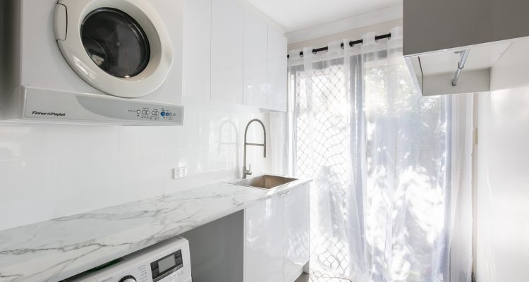 The laundry was given a modern make-over with new white, two-pac finish cabinetry, sleek bench tops, and an under-cabinet drying/hanging rail for clothes.